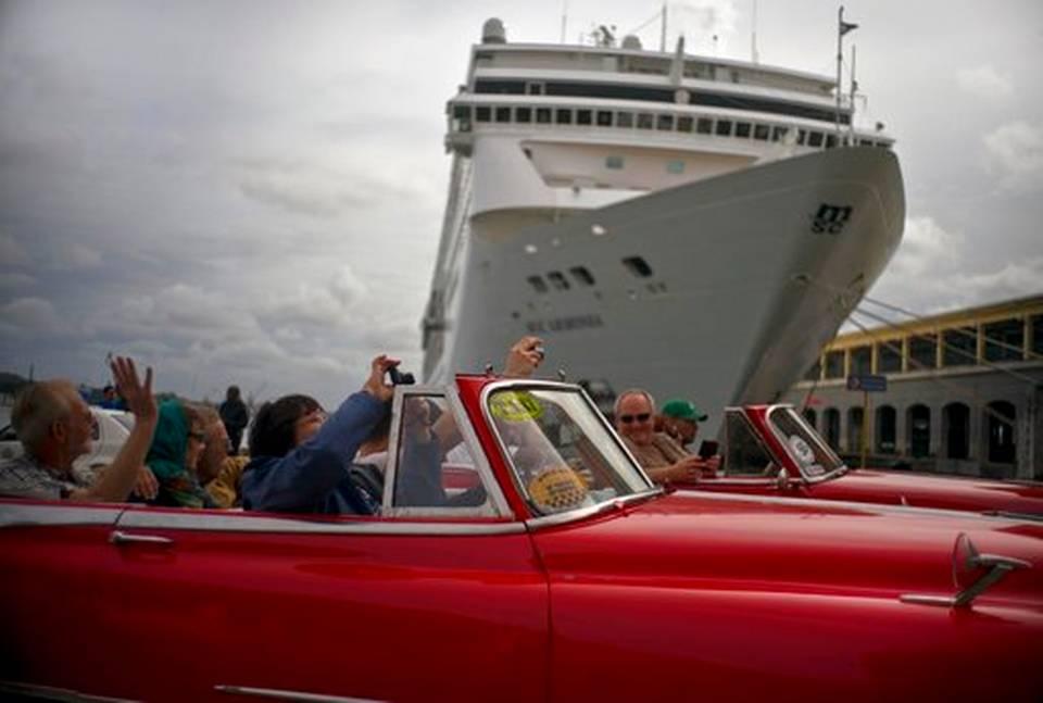 En esta imagen, tomada el 17 de enero de 2018, turistas que recorren La Habana en un auto cásico estadounidense pasan por delante de un crucero atracado en el puerto de la capital de Cuba. El boom turístico en Cuba comenzó en diciembre de 2014, poco después de que el expresidente Obama y su homólogo cubano, Raúl Castro, anunciaron que sus países restablecerían sus lazos diplomáticos y avanzarían hacia la normalización de sus relaciones.
